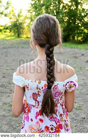 Portrait Of Beautiful Young Girl With Long Hair Braided In Braid, Dressed In Summer Dress Against Ba
