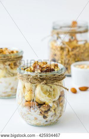 Healthy Breakfast. Oatmeal Granola With Greek Yogurt And Nuts Banana Muesli In Jars On Light Backgro