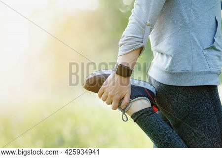 A Close Up Of A Woman Stretching Her Legs Before Going On A Run Through The Park.