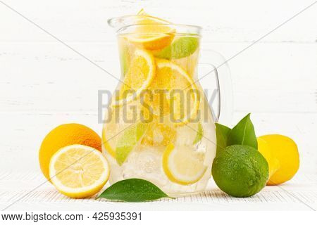 Fresh lemonade glass pitcher with ripe citrus fruits. With copy space