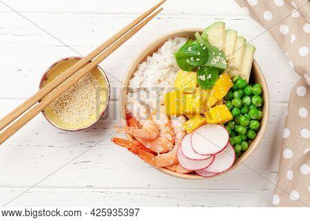 Poke bowl with shrimps, avocado and mango. Traditional hawaiian meal. Top view flat lay