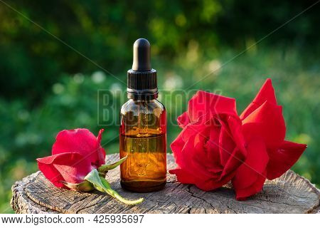 Rose Essential Oil Or Flavored Water Bottle. Red Rose Flowers.