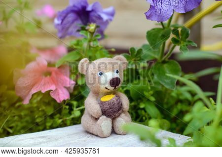 Toy Hand-made Cute Bear Sits With A Barrel Of Honey Among Flowers, Felting Wool