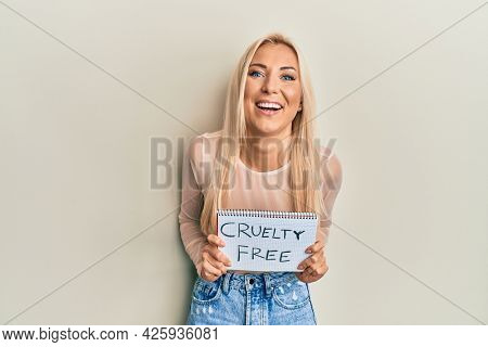 Young blonde woman holding cruelty free message banner smiling and laughing hard out loud because funny crazy joke.