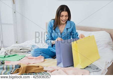 Cheerful Woman Looking Into Shopping Bags Near Plenty Of Clothing In Bedroom.