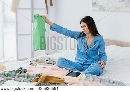 Dissatisfied Woman In Silk Pajama Looking At Vest Near Digital Tablet With Blank Screen On Bed.