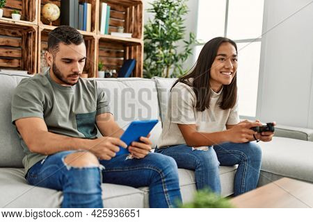 Young latin couple playing video game and using touchpad at home.