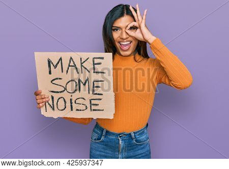 Young latin transsexual transgender woman holding make some noise banner smiling happy doing ok sign with hand on eye looking through fingers