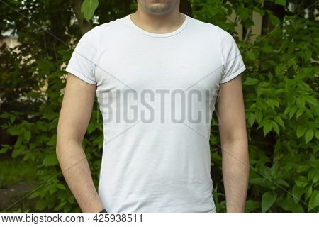 White Cotton T-shirt Mockup. Young Man In White T-shirt On Background Of Green Foliage. T-shirt Mock