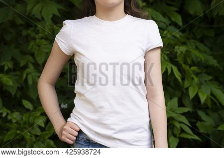 Mockup Of White Cotton T-shirt. Teenage Girl In White T-shirt On Background Of Green Foliage. T-shir