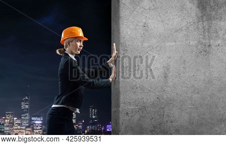 Beautiful Woman Architect Pushing Concrete Wall. Young Specialist In Safety Helmet On Night City Bac