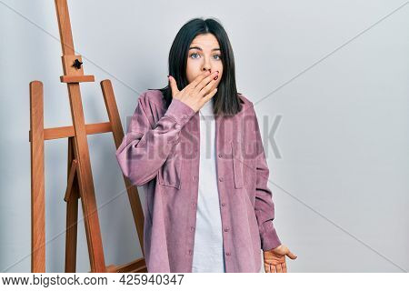 Young brunette woman standing by empty easel stand covering mouth with hand, shocked and afraid for mistake. surprised expression