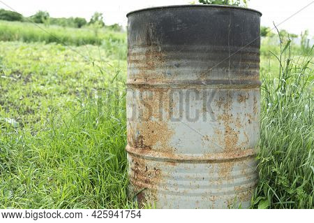 Old Rusty Metal Barrels And A Stove In The Backyard Of A Rural House Close-up On The Grass For Scrap
