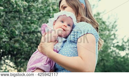 Careful Blonde Mother In Blue Dress Holds In Arms Crying Girl Kid And Lulls Standing Against Blurred