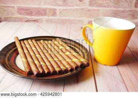Wafer Roll And Yellow Color Coffee Mug On Table
