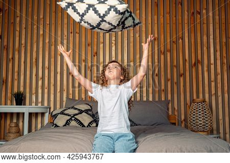Delighted Young Preschooler Girl With Long Loose Curly Hair Throws Black White Pillow On Large Grey