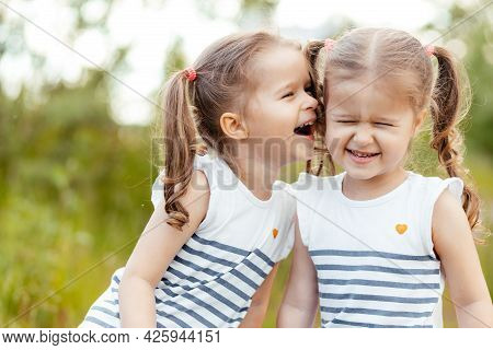 Little Twin Girls Play With Each Other In Nature