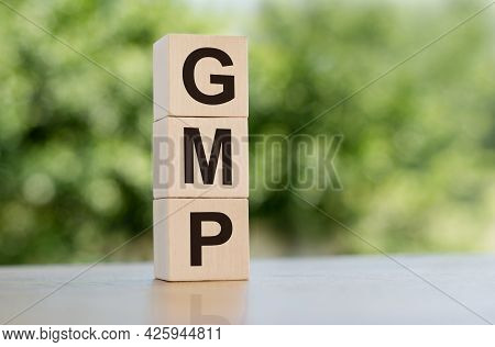 The Word Gmp - Abbreviation Of Good Manufacturing Practice, Built From Wooden Cubes Outdoors On The