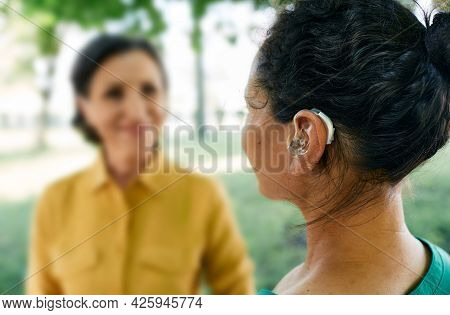 Adult Woman With A Hearing Impairment Uses A Hearing Aid To Communicate With Her Female Friend At Ci