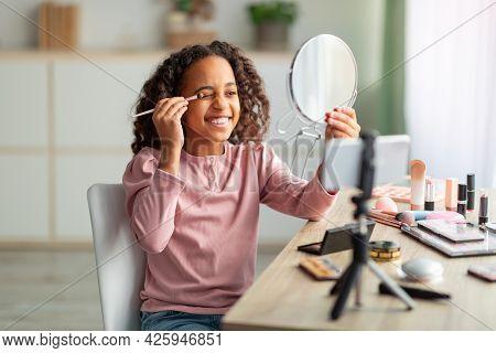 Beauty Blog For Teenagers. Joyful African American Girl Applying Eyeshadows And Recording Cosmetics