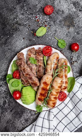 Grilled Munich Veal Sausages And Meat Rolls Wrapped Bacon, Chevapchichi Or Kofta Kebab. Ketogenic Di