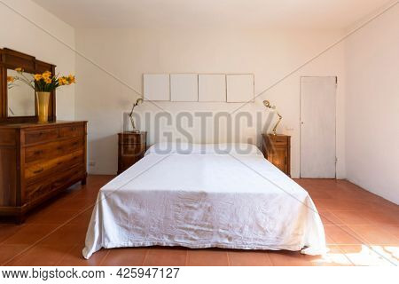 Interior of a double bedroom in a rustic and country style. We are in Italy. Nobody inside