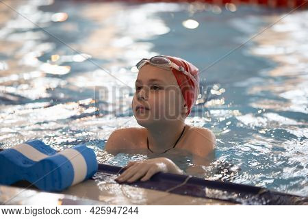 Boy In A Swimming Cap And Swimming Goggles In The Pool. The Child Is Engaged In The Swimming Section