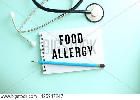 White Notepad With The Words Food Allergy And A Stethoscope On A Blue Background. Medical Concept