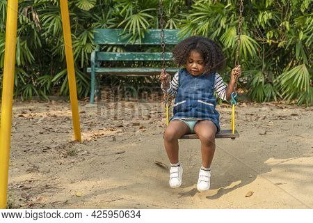 Adorable Dark Skinned Toddler Daughter Mixed-race Playing Swing In Playground While Looking Somethin