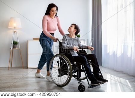 Full Length Portrait Of Young Mother And Her Impaired Son In Wheelchair Spending Time Together At Ho