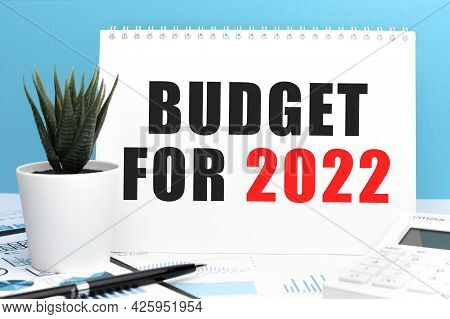 Text Budget For 2022 On Card. Pen And Calculator On Clipboard With Charts, Documents And Graphs. Bus