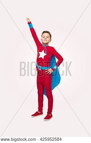 Full Body Of Excited Preteen Boy In Superhero Costume And Cape Standing Against White Background Wit