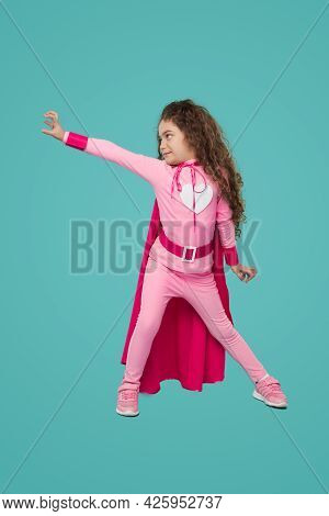 Full Body Of Little Girl In Pink Superhero Costume With Heart Emblem Outstretching Arm And Making De