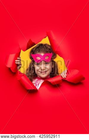 Cute Little Curly Haired Girl In Pink Masquerade Mask Smiling And Looking At Camera While Peeking Ou