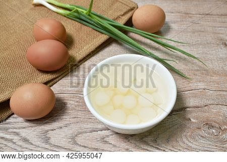 Pickled Single Garlic In Salt Water On Cup With Raw Egg And Spring Onion On Table