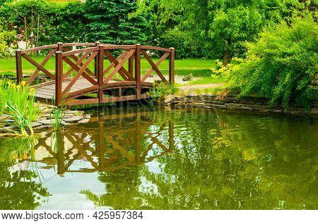Japanese garden, wooden bridge over the small pond. Garden landscaping, garden landscape view. Japanese garden design, summer garden in Japanese style
