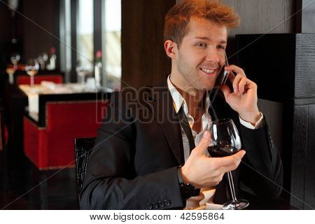 Happy young man in a black suit at a restaurant talking on the phone