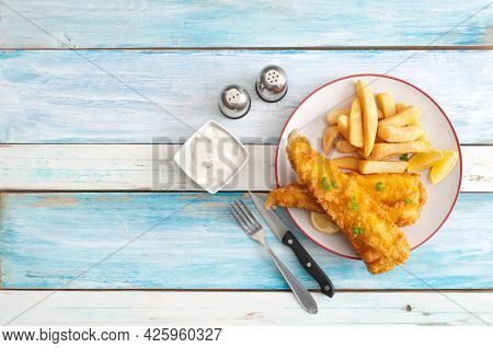 Deep Fried Cod With Chips On A Wooden Table