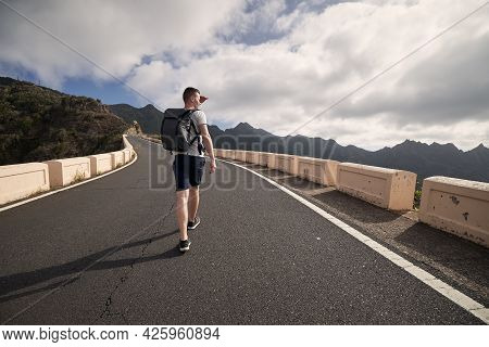 Rear View Of Man With Backpack On Mountain Road. Young Tourist Enjoys Trip On Sunny Day. Tenerife, C
