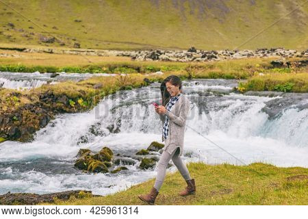 Woman walking by waterfall on Iceland. Girl tourist in casual clothing visiting icelandic nature landscape.