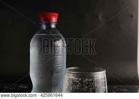 The Mineral Cold Water In The Glass And In The Plastic Bottle Stand Next To The Black Background Wit