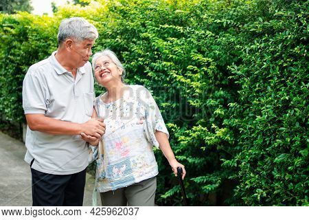 Happy Senior Couple Walking Together In The Garden. Old Elderly Using A Walking Stick To Help Walk B