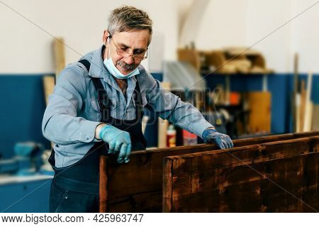 An Elderly Man Paints Wooden Boards With Dark Varnish In A Carpentry Workshop. A Pensioner In A Medi