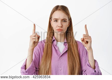 Close Up Portrait Of Disappointed Female Pointing Fingers Up, Grimacing Upset And Showing Bad Promo