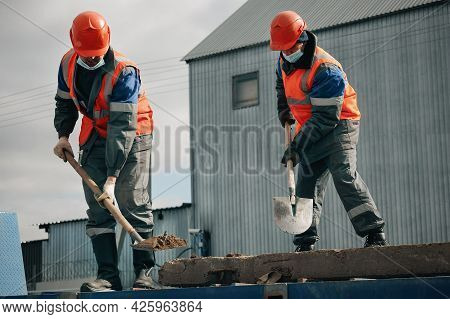 Two Workers In Hard Hats, Work Clothes And A Medical Mask Work With Shovels At A Construction Site.