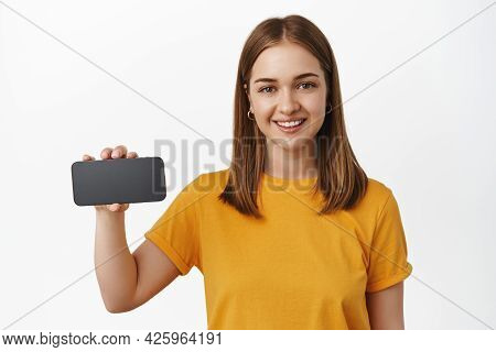 Portrait Of Attractive Young Woman Shows Horizontal Smartphone Screen, Video Game Or App Interface O