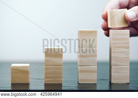Close-up Of Hand Of Person Stacking Wooden Blocks, Economic Growth And Business Success Concept
