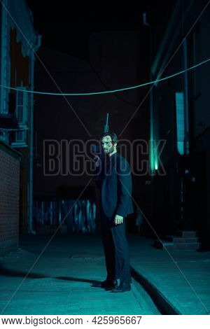The criminal world in the big city. Courageous man with a rifle stands on a backstreet of a city at night. Special agent.