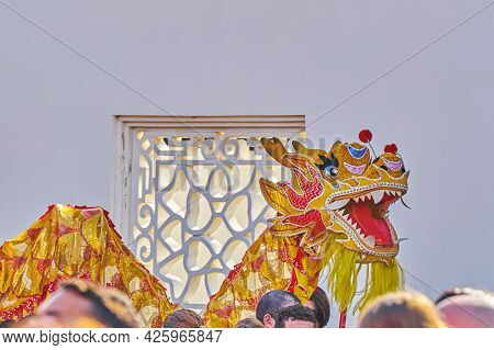 Traditional Chinese Golden Dragon Dancing Around Crowd In Chinese Garden During Celebration Of Chine