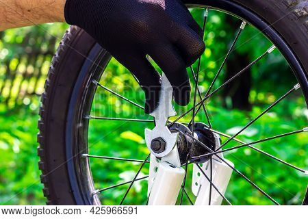 Bicycle Maintenance. Male Hands Spin A Bicycle Wheel. Wrench In Hand. Bicycle Repair. Replacing The
